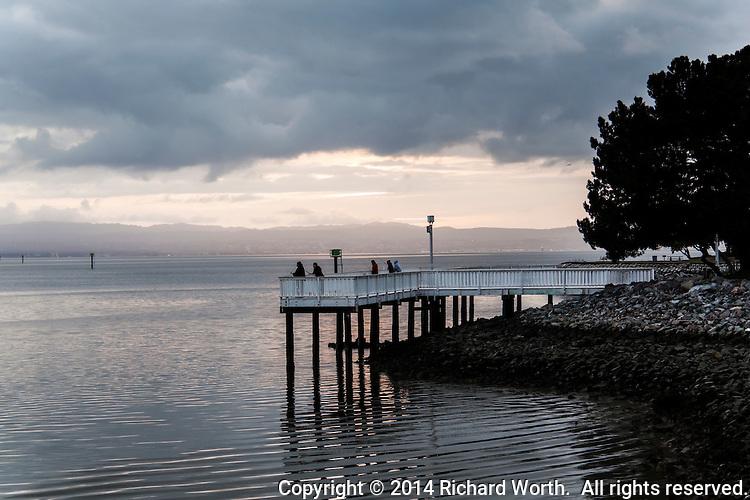 Fishermen with their poles as sunset draws near along the fishing pier at San Leandro Marina on San Francisco Bay.