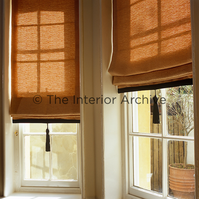 Burnt orange Roman blinds with black tassels hang in the bay window of the dining room