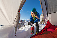 Female hiker melts snow outside of tent in winter, Moskenesøy, Lofoten Islands, Norway