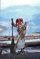 "A Mosuo woman in traditional costume on the shores of Lugu Lake in Yunnan. The Mosuo make their living by fishing and increasingly rowing tourists around the lake. Women from the Mosuo tribe do not marry, take as many lovers as they wish and have no word for ""father"" or ""husband"". But the arrival of tourism and the sex industry is changing their culture...PHOTO BY SINOPIX"