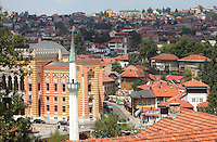 Minaret of the 16th century Hadzijska mosque, and behind, the National and University Library of Bosnia and Herzegovina, the national library, designed in 1891 by the Czech architect Karel Parik as the City Hall, and reopened as a library in 2014, Sarajevo, Bosnia and Herzegovina. This building, on the banks of the Miljacka river, is from the Austro-Hungarian period of the city. The building and many of its documents were damaged in 1992 during the Siege of Sarajevo in the Yugoslav War. Picture by Manuel Cohen