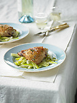 Two plates with a chicken thigh on a bed of sauteed leeks. On a white tablecloth with white wine and silverware.