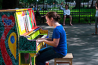 "New York, NY -  26 June 2010 Woman playing a piano in City Hall Park...Play Me I'm Yours"" is a musical installation by British artist Luke Jerram who has been touring the project globally since 2008. From 9am-10pm each day, 60 pianos will be available to play across New York City. Presented by Sing for Hope they are located in public parks, streets and plazas the pianos will be available until 5th July for any member of the public to play and engage with."