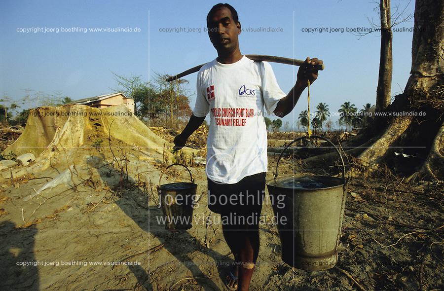 INDIEN Insel Little Andaman, Hutbay, Zerstoerung nach dem Tsunami Seebeben, Pater Pritam Toppo traegt Wasser - INDIA Little Andaman island, Hutbay, destroyed houses after Tsunami sea quake, priest Pritam Toppo carry water