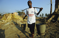 INDIEN Insel Little Andaman, Hutbay, Zerstoerung nach dem Tsunami Seebeben, Pater Pritam Toppo traegt Wasser - INDIA Little Andaman island, Hutbay, destroyed houses after Tsunami sea quake, priest Pritam Toppo carry water