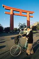 A visitor pauses near the giant torii gate at Heian Jingu shrine in Kyoto.