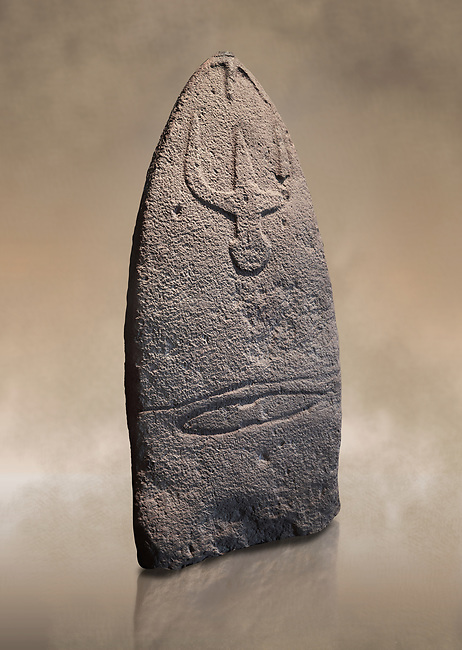 Late European Neolithic prehistoric Menhir standing stone with carvings on its face side. The representation of a stylalised male figure starts at the top with a long nose from which 2 eyebrows arch around the top of the stone. below this is a carving of a falling figure with head at the bottom and 2 curved arms encircling a body above. at the bottom is a carving of a dagger running horizontally across the menhir. Excavated from Genna Arrele II. Menhir Museum, Museo della Statuaria Prehistorica in Sardegna, Museum of Prehoistoric Sardinian Statues, Palazzo Aymerich, Laconi, Sardinia, Italy