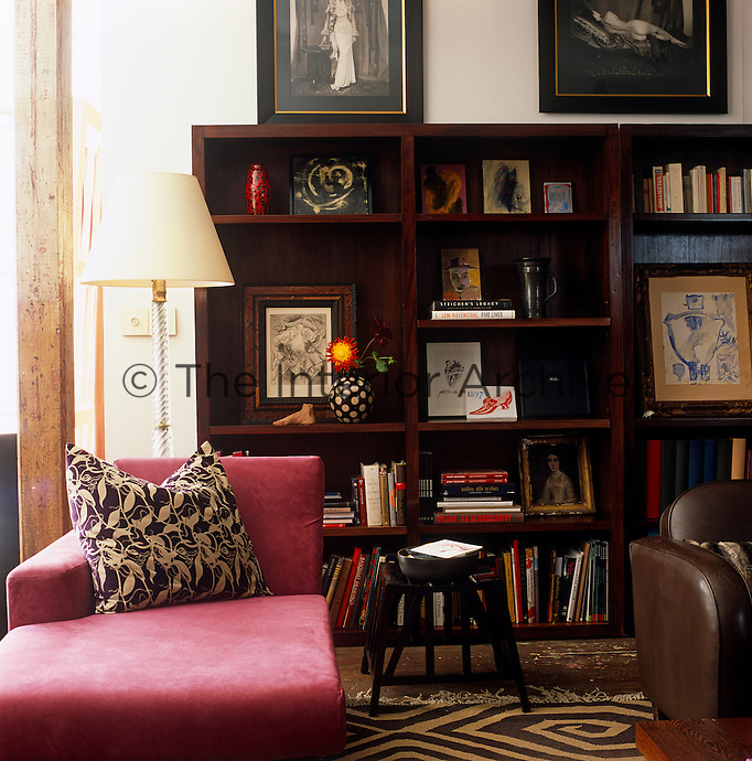 Artwork by Ross Bleckner, Pablo Picasso and Julian Schnabel, amongst others, is displayed on a large wooden bookcase in the living room