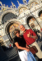 Middle age tourist couple brightly dressed in front of the Famous St Marks Church in San Marcos Plaza in romantic Venice Ital