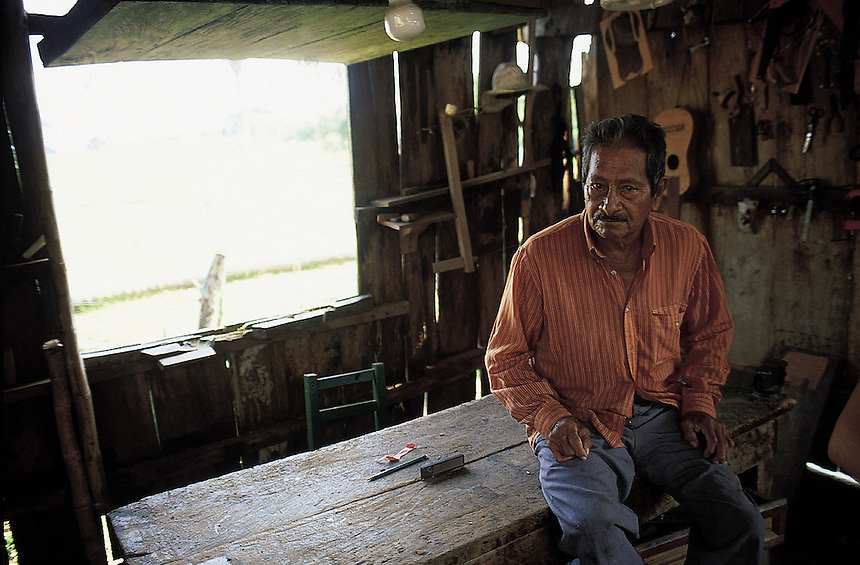 Don Esteban Ultrera one of the most respected requinteros and craftsman sits at his work table in his workshop which is in a small farm near Santiago de Tuxtla, Veracruz, Mexico 2002.  The requinto is the small guitar used in Son Jarocho.