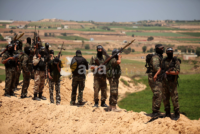 Palestinian militants of Al-Nasser Brigades, the armed wing of the Popular Resistance Committees, hold up their weapons during a military march, in Beit Hanoun in the northern Gaza Strip, June 16, 2015. Photo by Ashraf Amra