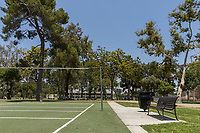 A bench (and trash can) sit next to the artificial turf volleyball courts at South Gate Park.