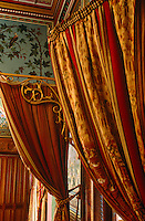 A set of grand curtains is attached to gilded brackets above a doorway
