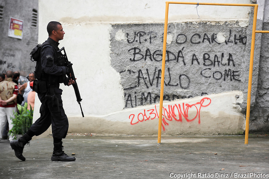 Beggining of operations of the UPP - Pacifying Police Unit inside Favela do Caju in the harbor area of Rio de Janeiro, Brazil - Policeman belonging to BOPE crosses a soccer field - Unidade de Polícia Pacificadora, also translated as Police Pacification Unit, abbreviated UPP, a law enforcement and social services program which aims at reclaiming territories, more commonly favelas, controlled by gangs of drug dealers. Batalhão de Operações Policiais Especiais (BOPE), Special Police Operations Battalion is a special forces unit of the Military Police of Rio de Janeiro State, Brazil. Due to the nature of crime in favelas, BOPE units have extensive experience in urban warfare as well as progression in confined and restricted environments. It also utilizes equipment deemed more powerful than traditional civilian law enforcement.