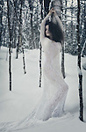 Beautiful woman in white sheer long lace dress leaning against a birch tree in snow covered winter nature scenery Image © MaximImages, License at https://www.maximimages.com