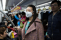 Ada, a student in Beijing, rides the city's subway system. Many residents now not only wear the masks outdoors but also in indoor public spaces and on public transportation. PM2.5 reading - 191 - Unhealthy