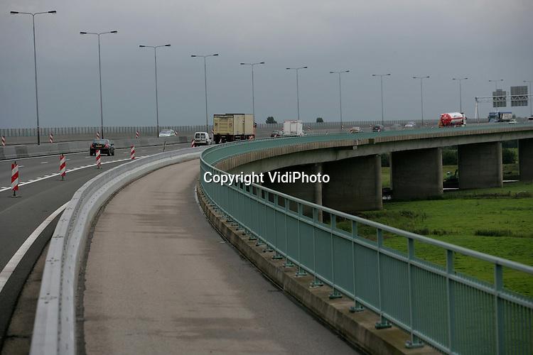 Foto: VidiPhoto..HETEREN - De brug over de Rijn in de snelweg A50 (Apeldoorn-Den Bosch) is er slecht aan toe. In het beton zitten scheuren. Rijkswaterstaat gaat met spoed een extra steunconstructie onder de brug plaatsen. Een inspectie van de brug bij Heteren in de afgelopen week heeft de tekortkomingen aangetoond. De Rijnbrug is bijna veertig jaar oud en niet berekend op de explosieve groei van vooral het vrachtverkeer. Om de belasting van de brug te verminderen en om ruimte te hebben voor de werkzaamheden zijn de spitsstroken op de brug al gesloten.