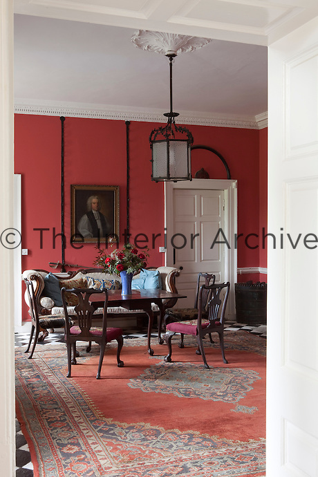 The entrance hall is furnished with an Irish Georgian table and chairs with hand-stitched tapestry seats