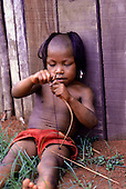 A-Ukre village, Brazil. Kayapo boy making a toy bow and arrow; Xingu Indian Reserve.