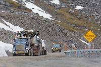 Push truck assists a heavy load as truckers climb Atigun pass in the Brooks range, James Dalton highway, Alaska.