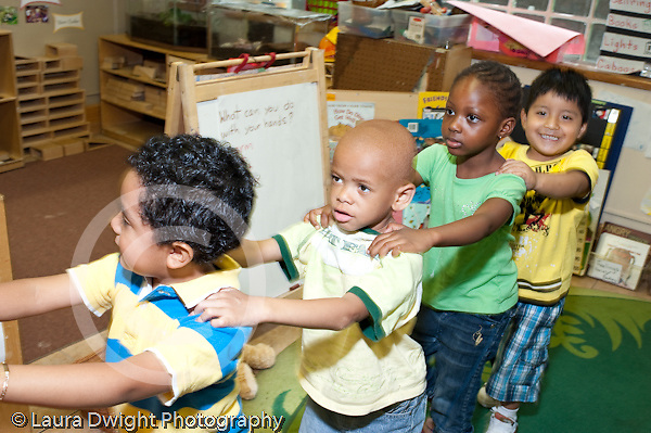 Education Preschool 3-5 year olds circle time group of children walking with hands on each others shoulders horizontal