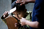 A young boy combs his hair and uses the only mirror available, in preparation for school at an orphanage in Pokhara, Nepal.
