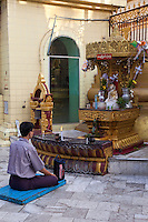 Myanmar, Burma, Yangon.  Sule Pagoda.  Early-Morning Worshiper Praying in front of Buddha Shrine.