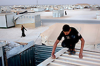 A man on the roof of a container at Zaatari Refugee Camp. Approximately two million people have fled the conflict in Syria. At least 130,000 of them live in Zaatari Refugee Camp, although it was designed to house 60,000, and a further 2,000 people arrive each day.