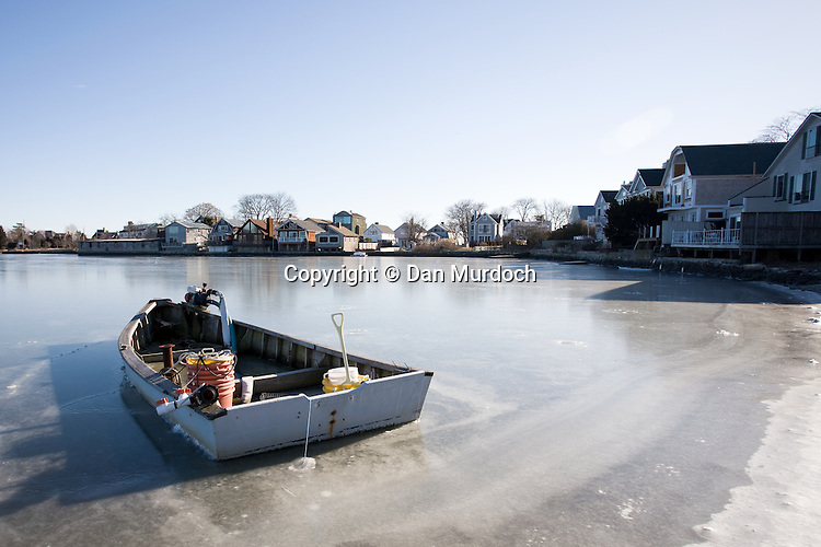 Small clam boat frozen in saltwater pond