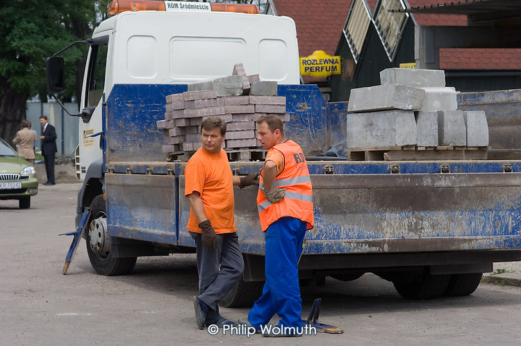 Building workers, working on refurbishment of a square in the Polish city of Krakow, with a delivery of concrete blocks.