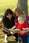 Two women and child (18-21 months) reading book