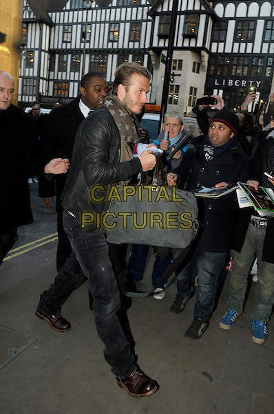 David Beckham arriving at H&M to launch his new Bodywear Collection, Oxford Street, London, England..February 1st 2012.full length black leather jacket jeans denim grey gray bag star stars scarf side profile stubble facial hair minder bodyguard security fans crowd.CAP/IA.©Ian Allis/Capital Pictures.
