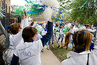 Cheerleaders facetiously cheering selling of water in plastic bottles. MayDay Parade and Festival. Minneapolis Minnesota USA