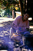 Koatinemo village, Brazil. Assurini Indian woman, Mira, applying vegetable glaze (resin from the Jatoba tree) over a fire.