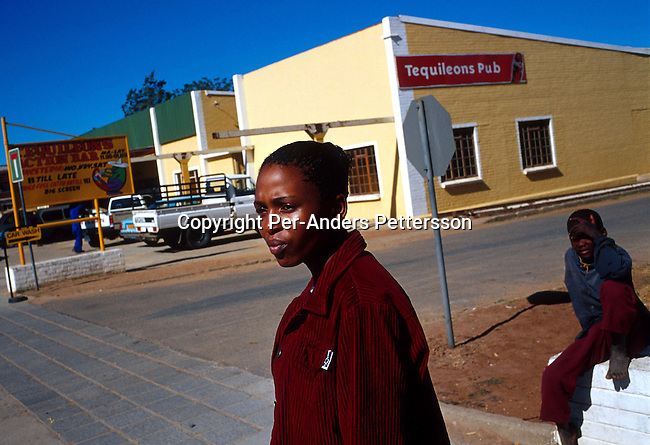 Thenjiwe Bosman a 24-year old worker for the ANC passes the Tequileons Pub, a whites only bar on June 20, 2001 in Vryburg, South Africa. Thenjive is scared of walking in the streets of Vryburg after dark because of racial attacks. Vryburg, a small and very conservative farming town about 400 km west of Johannesburg has had a lot of high profile racist attacks since the democratic elections in 1994. A black boy is currently in prison after stabbing a white boy in Vryburg High School.The school has had a problem with  the integration of the black pupils in the former only white school. Some bars and restaurants are still for whites only. South Africa is still battling racism after seven years of a democraticly elected black government..Photo: Per-Anders Pettersson/iAfrika Photos