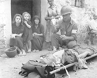 Private Roy Humphrey of Toledo, Ohio, is being given blood plasma by Pfc. Harvey White of Minneapolis, Minn., after he was wounded by shrapnel, on 9 August 1943 in Sicily.  Wever. (Army)<br /> NARA FILE #:  111-SC-178198<br /> WAR & CONFLICT BOOK #:  1025