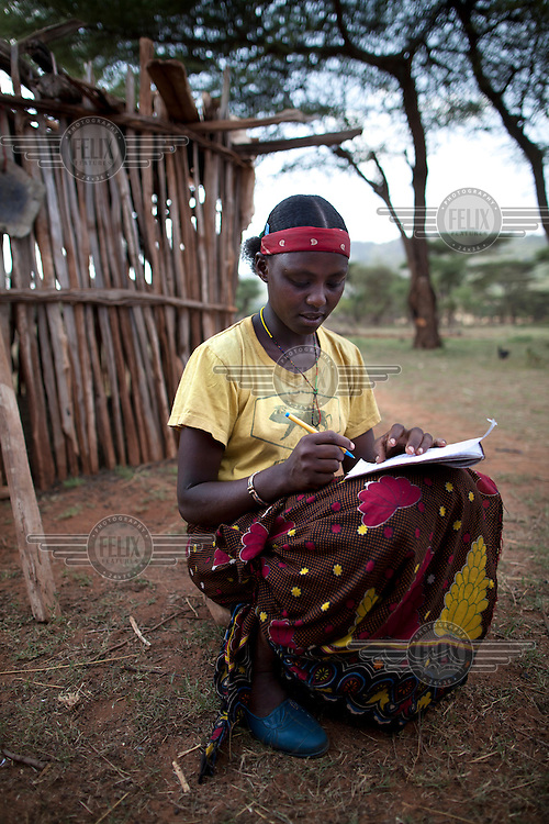 A young woman sits outside and writes out her homework.