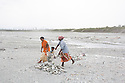 India – West Bengal: Former tea workers collecting pebbles and stones along the Diana riverbed at Red Bank Tea Estate, in the Dooars region. The garden, which houses 888 workers out of a population of 5,000 people, has been closed since 2013, forcing its workers to resort to stonecrushing along the riverbanks in order to survive. At the end of 2014, the tea estate was taken over by the government, in order to initiate emergency relief procedures for its population.