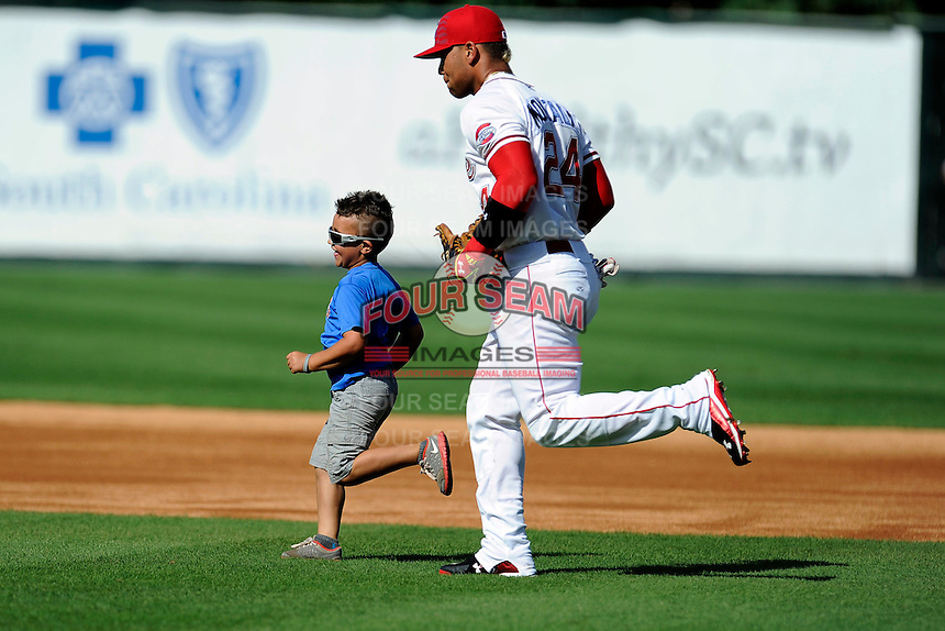 Second baseman Yoan Moncada (24) of the Greenville Drive runs onto the field with a youth player in a game against the Savannah Sand Gnats on Sunday, July 5, 2015, at Fluor Field at the West End in Greenville, South Carolina. The Cuban-born 19-year-old Red Sox signee has been ranked the No. 1 international prospect in baseball by Baseball America. Savannah won, 8-6. (Tom Priddy/Four Seam Images)