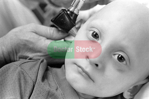 Serious portrait of three year old boy with cancer being examined; bald from treatment