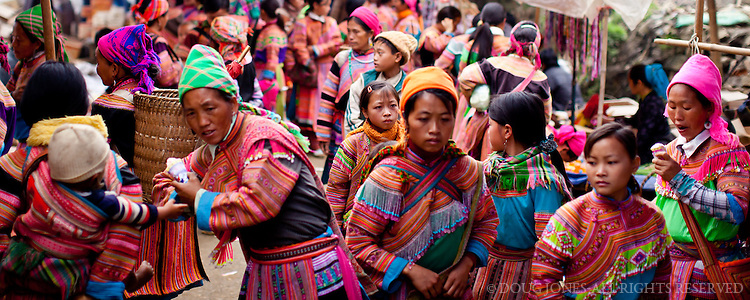 Weekly market days attract the women from different Hmong tribes in the hill country of northeastern Vietnam.  The women in this photo are mostly from the Flower Hmong and Black Hmong tribes.