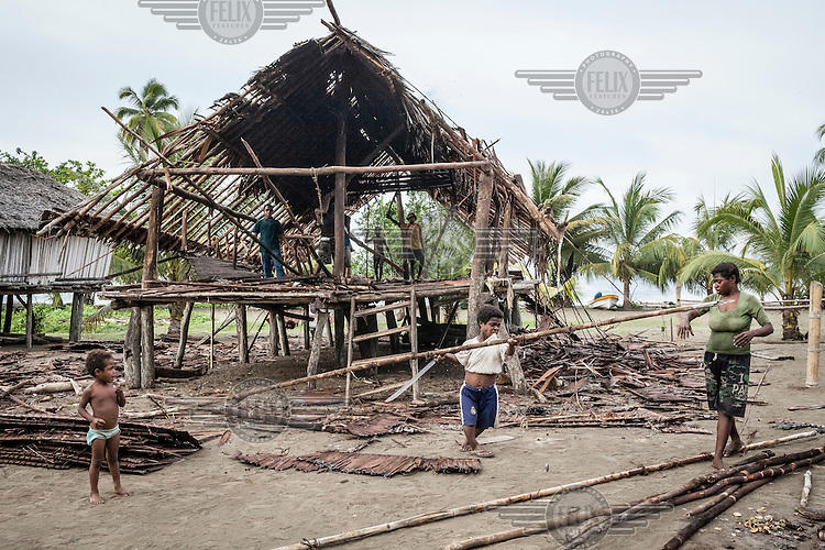 Villagers dismantle an old house.