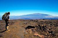 Hiker on the trail to the summit of Mauna Loa volcano 13679' Hawaii, USA Volcanoes National Park the Big Island of Hawaii, USA Mauna Kea in the distance