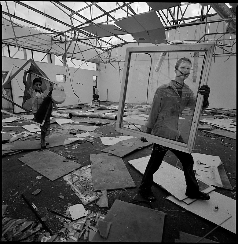Neve Dekalim, Gaza strip, Sept 12 2005.Thousands of Palestinians from nearby Khan Younes enter Neve Dekalim at dawn to see this former Jewish settlement for the first time. Most people tried to find anything still usable in the ruins of the buildings destroyed by the Israeli army.