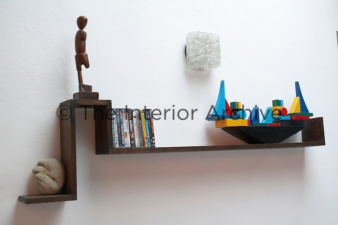 A wooden figure and model boat are displayed on a shaped wall shelving in the living area
