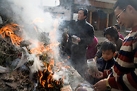 Buddhist pilgrims burn pine, nuts, candy, and milk, as an offering at a temple outside the Labrang Monastery during Monlam Festival in Xiahe, Gansu, China.