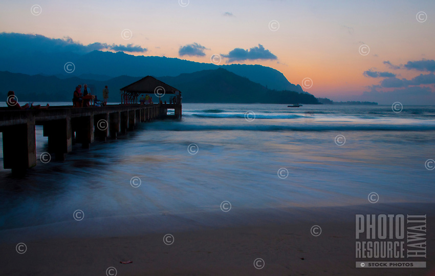 Relaxing on the pier at Hanalei Beach Park on the North Shore of Kauai, with a golden glow sunset lighting up the water's edge and the sky over Na Pali.