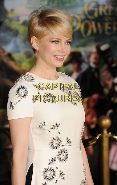 """Michelle Williams.at the world premiere of Disney's """"OZ The Great And Powerful"""" at El Capitan Theatre in Hollywood, California on February 13th, 2013. .half length white dress short sleeved flowers  embellished jewelled beaded knickers hair smiling profile .CAP/ROT/TM.©Tony Michaels/Roth Stock/Capital Picturess"""