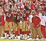 San Francisco 49ers defensive tackle DeVone Claybrooks (92) and defensive back Dwaine Carpenter (35) cheer wide receiver Terrell Owens (81) as he make big run on Sunday, October 19, 2003, in San Francisco, California. The 49ers defeated the Buccaneers 24-7.