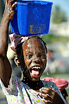 Eight-year old Caitland Dirocher carries water home in a camp for families left homeless from Haiti's January 12 earthquake. The camp, in the Martissant section of Port-au-Prince, houses hundreds of displaced families who are receiving medical care and other services from Dominican solidarity groups supported by the ACT Alliance.